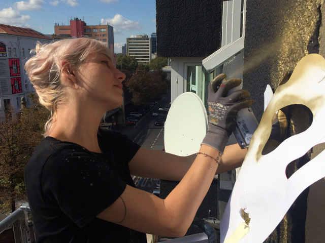 Foto di NeSpoon realizzando un murales