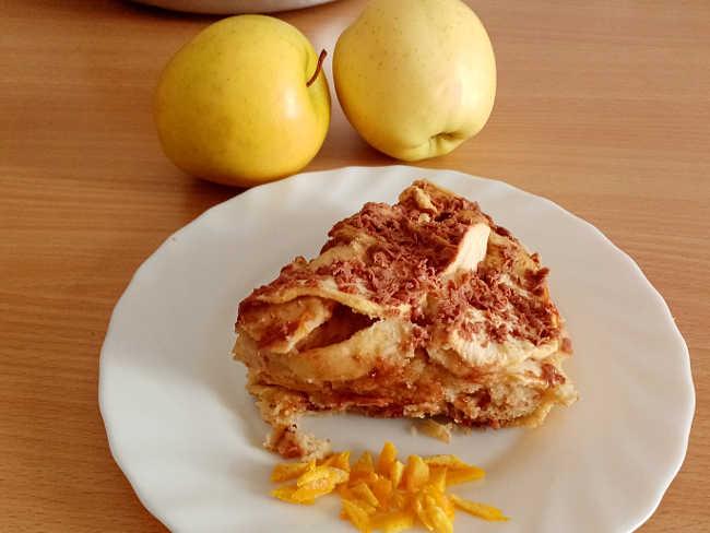 2 La Torta di mele con scorza d'arancia e cioccolato al latte  senza burro una vera golosità. Una ricetta veloce e buona. La torta di mele un dolce che non ha stagione sempre apprezzata anche in tutte le sue varianti. Io l'ho preparata senza olio e senza burro ed  è risultata ugualmente sofficissima. A proposito di torte di mele vi lascio alcune mie preparazioni: laTorta di mele con scorza d'arancia e cioccolato al latte  senza burro,  Torta di mele con crema pasticcera senza burro ricetta semplice e buona e la Torta di mele con confettura di albicocche golosissima. Torta di mele con scorza d'arancia e cioccolato al latte  senza burro  Per uno stampo in alluminio di circa 20 centimetri  Ingredienti per la torta di mele 3 uova  3 mele 120 g di zucchero 170 g di farina 00 50 g di cioccolato al latte  100 g di acqua  1 bustina di lievito la buccia di un'arancia non trattata  un pizzico di sale olio o burro e farina per lo stampo (altrimenti carta forno o staccante) Procedimento e preparazione per Torta di mele con scorza d'arancia e cioccolato al latte  senza burro. Per prima cosa lavate bene l'arancia. Verificate che siano non trattate e quindi la scorza edibile solitamente è scritto sulla confezione. Tagliate la scorza con un coltello affilato senza la parte bianca e poi tagliatela con un coltello anche non troppo finemente. mettete sul fuoco un pentolino con l'acqua e la scorza e lasciate cuocere una decina di minuti. Spegnete fate raffreddare e colate. L'idea di usare la scorza d'arancia è nata dal fatto che avevo tenuto da parte già prima la scorza e messa nel congelatore. Avendo comprato delle arance non trattate e bevuto la spremuta ho pensato di tenere la scorza e in modo da averla a disposizione anche d'estate per profumare i dolci. Mettete in unsa ciotola le uova, lo zucchero, l'acqua tiepida delle arance ed un pizzico di sale. Pulite e lavate le mele. tagliatele a fette e spolverate con un cucchiaio di zucchero. Giratele in modo che non anneriscano. Montate 